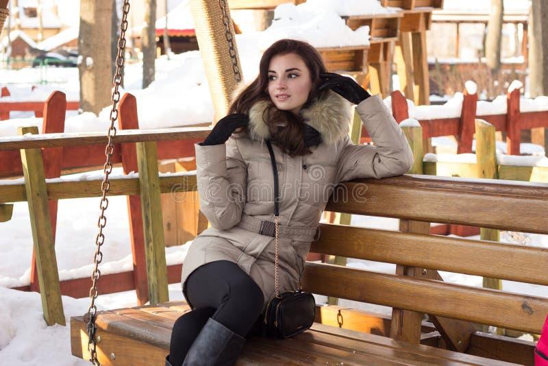 Νέα γυναίκα στη συνεδρίαση χειμερινών πάρκων στον πάγκο στοκ φωτογραφίες