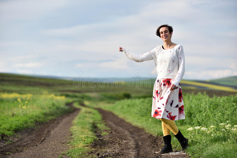 Νέα γυναίκα στη φούστα που κάνει ωτοστόπ κοντά σε έναν δρόμο επαρχίας στοκ εικόνες