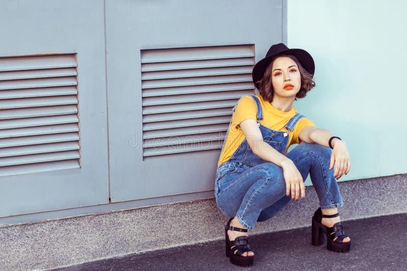 Νέα γυναίκα στις μπλε φόρμες τζιν και κίτρινη μπλούζα με την αισθησιακή εξέταση μαύρων καπέλων τη κάμερα θέτοντας κοντά σε βιομηχ στοκ εικόνα με δικαίωμα ελεύθερης χρήσης