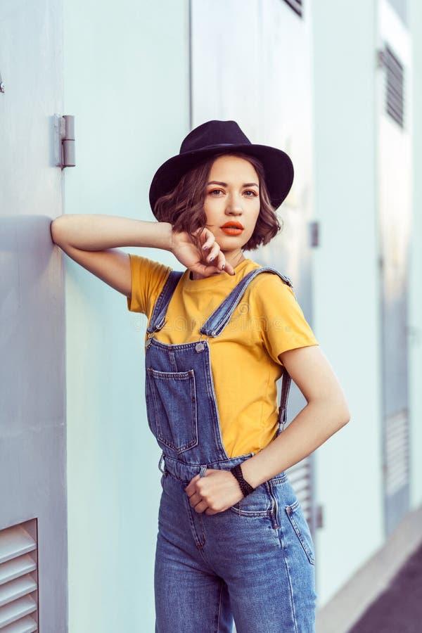 Νέα γυναίκα στις μπλε φόρμες τζιν και κίτρινη μπλούζα με την αισθησιακή εξέταση μαύρων καπέλων τη κάμερα θέτοντας κοντά σε βιομηχ στοκ εικόνες με δικαίωμα ελεύθερης χρήσης