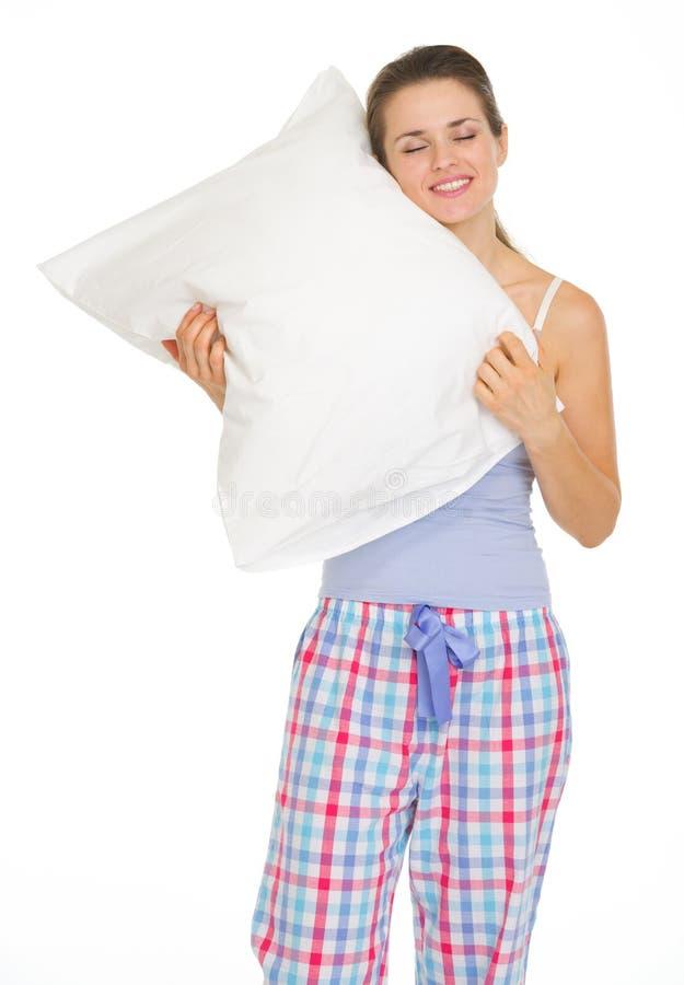 Νέα γυναίκα στις πυτζάμες που απολαμβάνει το άνετο μαξιλάρι στοκ φωτογραφία
