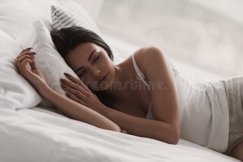 Νέα γυναίκα στις πυτζάμες που κοιμούνται στο κρεβάτι στο σπίτι στοκ φωτογραφίες
