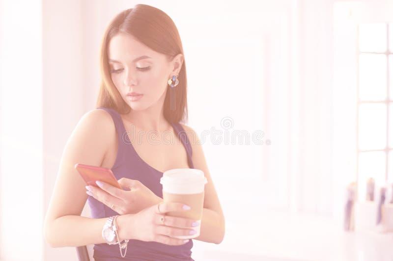 Νέα γυναίκα στον καφέ κατανάλωσης καφέδων και ομιλία στο κινητό τηλέφωνο στοκ φωτογραφία με δικαίωμα ελεύθερης χρήσης