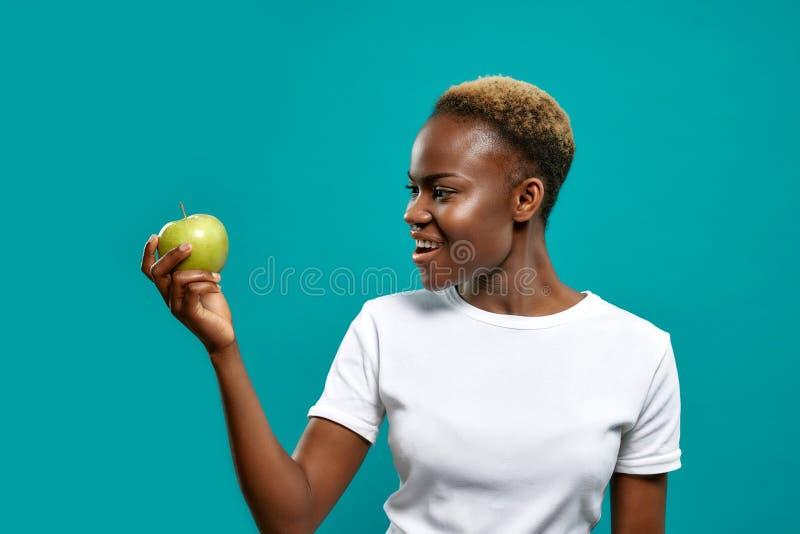 Νέα γυναίκα στο άσπρο πουκάμισο που κρατά το φρέσκο πράσινο μήλο στοκ εικόνα