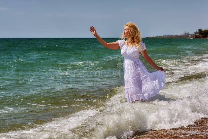 Νέα γυναίκα στο άσπρο ρομαντικό φόρεμα στην παραλία στοκ εικόνες