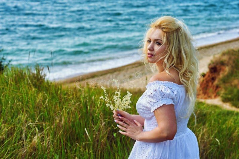 Νέα γυναίκα στο άσπρο ρομαντικό φόρεμα στην παραλία στοκ φωτογραφία με δικαίωμα ελεύθερης χρήσης