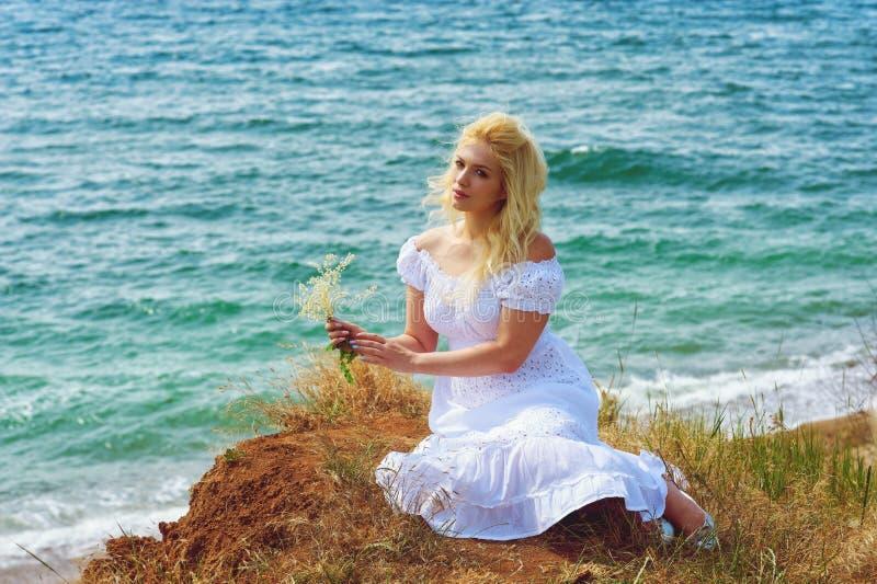 Νέα γυναίκα στο άσπρο ρομαντικό φόρεμα στην παραλία στοκ φωτογραφία