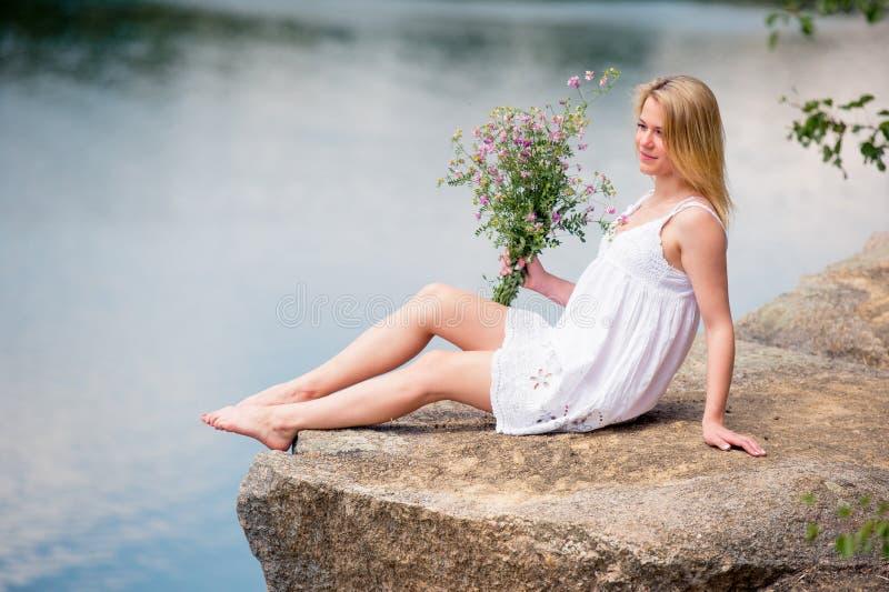 Νέα γυναίκα στο άσπρο φόρεμα δαντελλών στην παραλία Κάθεται με το bouq στοκ εικόνα με δικαίωμα ελεύθερης χρήσης