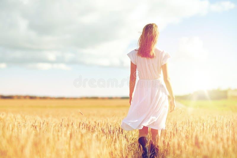 Νέα γυναίκα στο άσπρο φόρεμα που περπατά εμπρός στον τομέα στοκ φωτογραφία