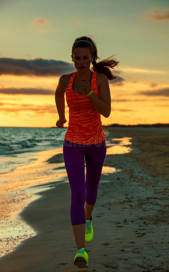 Νέα γυναίκα στο αθλητικό εργαλείο στην παραλία ηλιοβασιλέματος στοκ φωτογραφίες με δικαίωμα ελεύθερης χρήσης