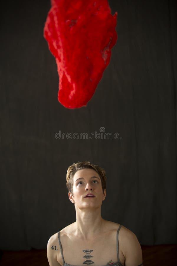 Νέα γυναίκα στο ασημένιο φόρεμα με το κόκκινο μαντίλι που επιπλέει ανωτέρω στοκ εικόνες