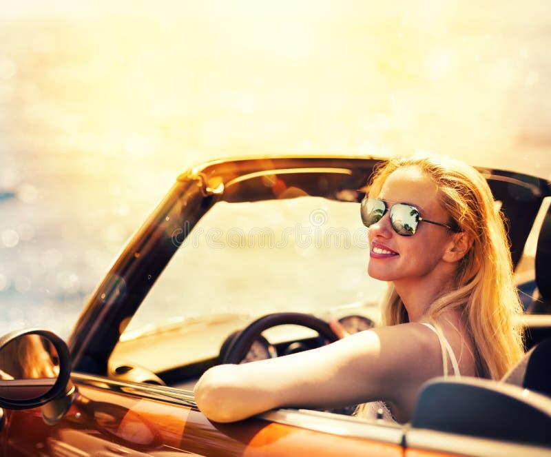 Νέα γυναίκα στο αυτοκίνητο καμπριολέ κοντά στη θάλασσα στοκ φωτογραφία
