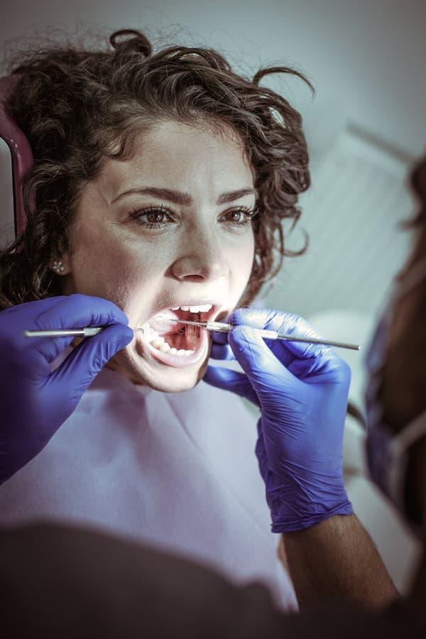 Νέα γυναίκα στο γραφείο οδοντιάτρων ` s για τη στερεότυπη εξέταση στοκ εικόνες