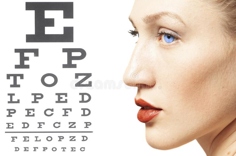 Νέα γυναίκα στο διάγραμμα δοκιμής όρασης στοκ φωτογραφίες