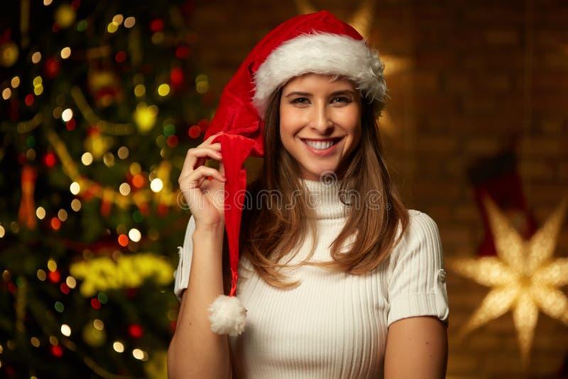 Νέα γυναίκα στο καπέλο santa με τα φω'τα Χριστουγέννων στοκ φωτογραφία