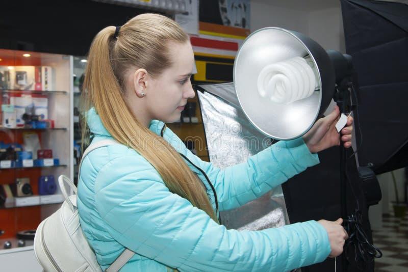 Νέα γυναίκα στο κατάστημα phototechnique που κοιτάζει στα επίκεντρα στοκ φωτογραφίες