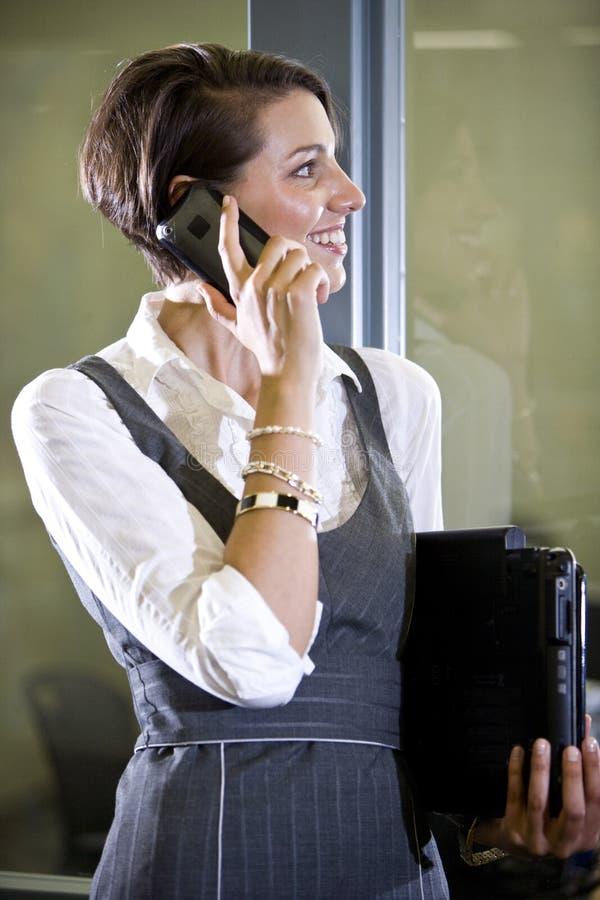 Νέα γυναίκα στο κινητό τηλέφωνο που υπερασπίζεται την πόρτα γυαλιού στοκ εικόνες με δικαίωμα ελεύθερης χρήσης
