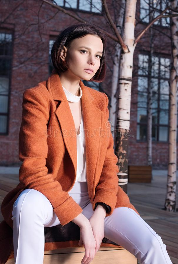 Νέα γυναίκα στο κόκκινο παλτό και τα άσπρα εσώρουχα που κάθεται σε έναν ξύλινο πάγκο οδός στοκ εικόνες με δικαίωμα ελεύθερης χρήσης