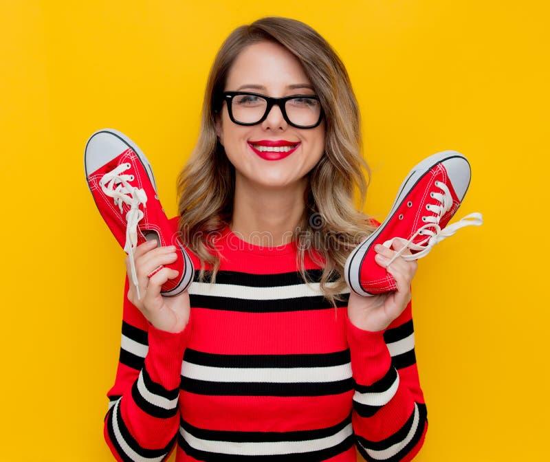 Νέα γυναίκα στο κόκκινο ριγωτό πουλόβερ με τα gumshoes στοκ εικόνες