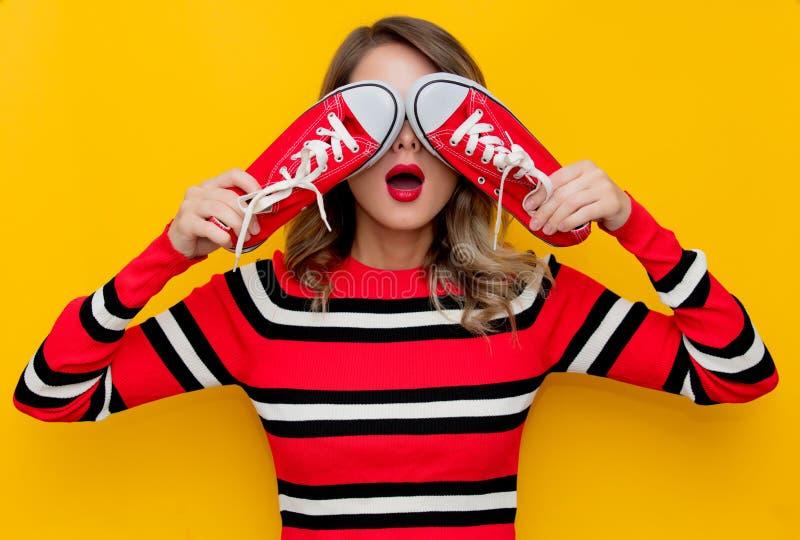 Νέα γυναίκα στο κόκκινο ριγωτό πουλόβερ με τα gumshoes στοκ εικόνα