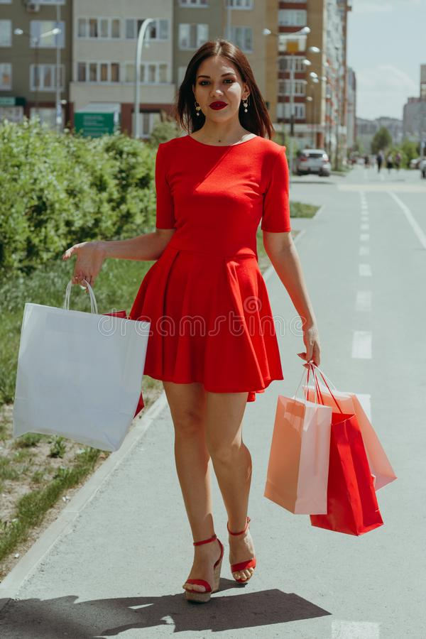 νέα γυναίκα στο κόκκινο φόρεμα που περπατά κάτω από τις τσάντες αγορών εκμετάλλευσης οδών στοκ εικόνα με δικαίωμα ελεύθερης χρήσης