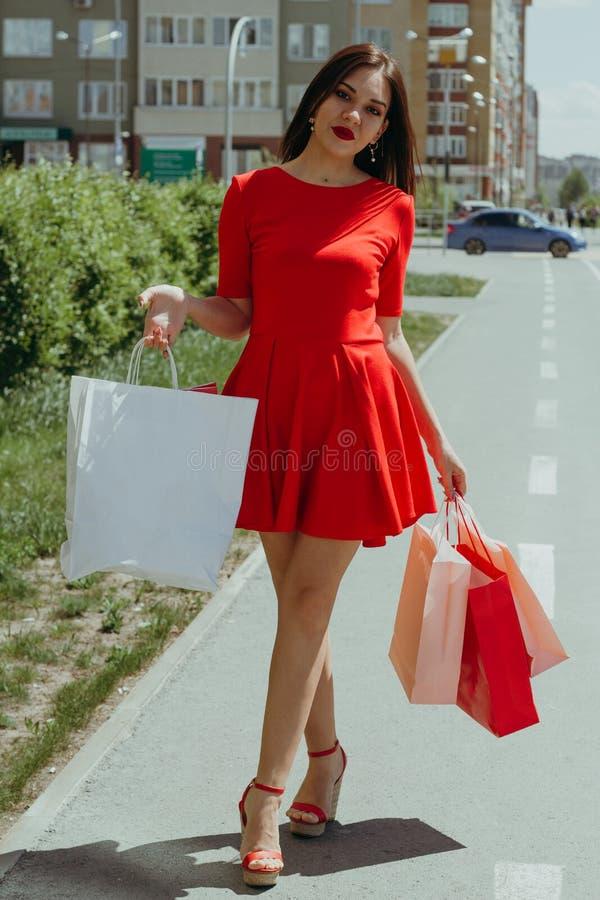 Νέα γυναίκα στο κόκκινο φόρεμα που περπατά κάτω από τις τσάντες αγορών εκμετάλλευσης οδών στοκ εικόνες