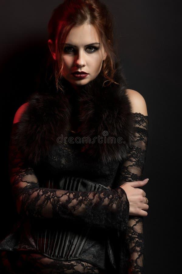 Νέα γυναίκα στο μαύρο γοτθικό κοστούμι στοκ φωτογραφία