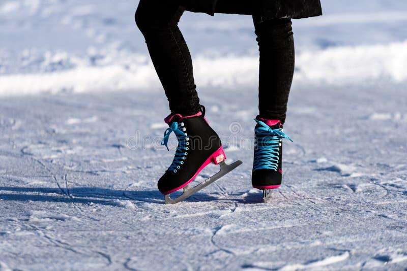 νέα γυναίκα στο μαύρο παλτό που κάνει πατινάζ στην παγωμένη λίμνη στο χιόνι στοκ εικόνα