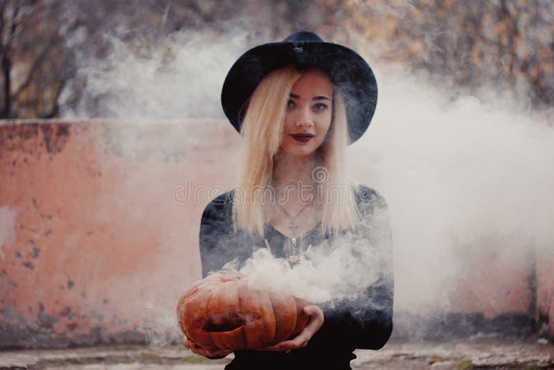 Νέα γυναίκα στο μαύρο παλτό που κρατά την κολοκύθα αποκριών με τον άσπρο καπνό που έρχεται από μέσα από το το φθινόπωρο στοκ εικόνες