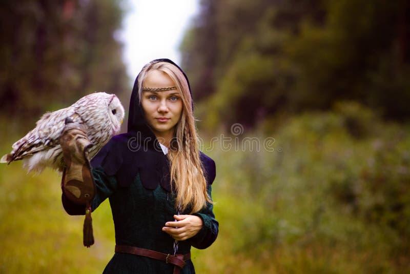 νέα γυναίκα στο μεσαιωνικό φόρεμα με μια κουκουβάγια στο βραχίονά της στοκ εικόνες