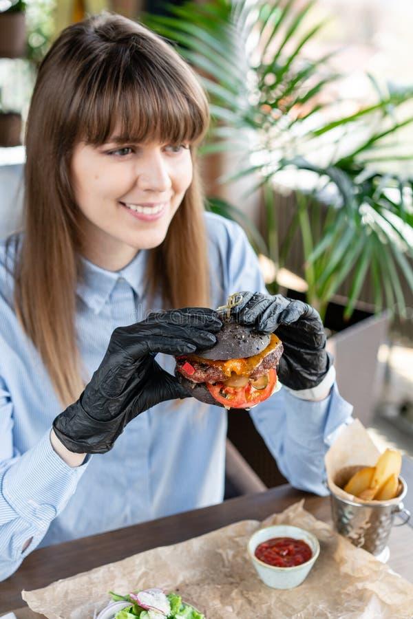 Νέα γυναίκα στο μπλε πουκάμισο και τα μαύρα γάντια που τρώει το εύγευστο juicy χάμπουργκερ με την μπριζόλα βόειου κρέατος Burgers στοκ φωτογραφία