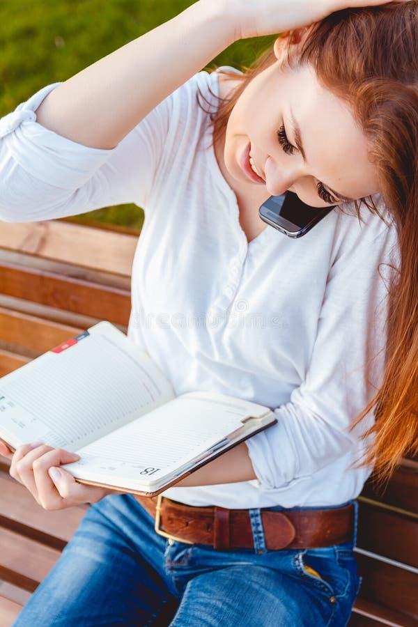 Νέα γυναίκα στο πάρκο με το τηλέφωνο στοκ φωτογραφία με δικαίωμα ελεύθερης χρήσης