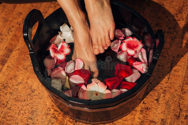 Νέα γυναίκα στο πόδι-λουτρό στο ασιατικό νερό χορταριών για το σώμα detox στοκ εικόνα με δικαίωμα ελεύθερης χρήσης