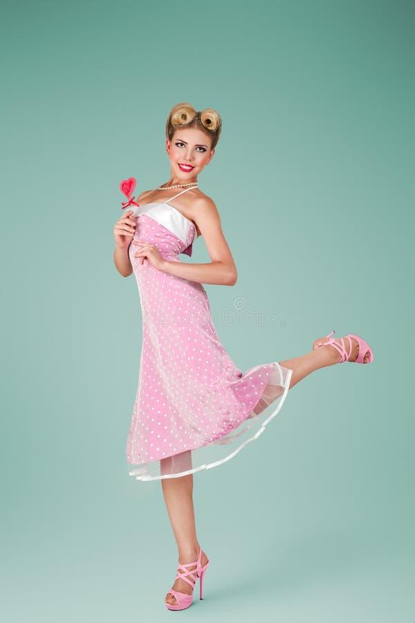 Νέα γυναίκα στο ρόδινο εκλεκτής ποιότητας φόρεμα στοκ εικόνα