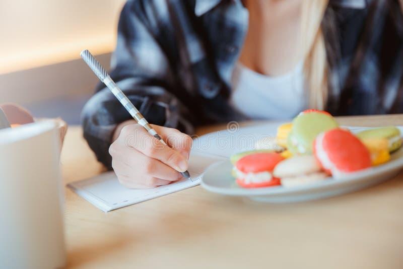 Νέα γυναίκα στο σπίτι στην κουζίνα που παίρνει τις σημειώσεις σε μια κινηματογράφηση σε πρώτο πλάνο σημειωματάριων στοκ εικόνα
