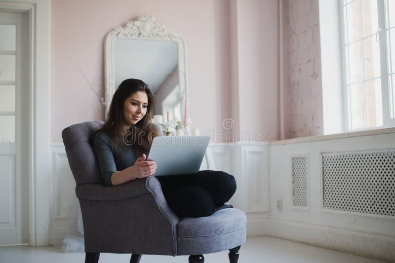 Νέα γυναίκα στο σπίτι στη χαλάρωση πολυθρόνων στο lliving δωμάτιό της με το lap-top στοκ φωτογραφία με δικαίωμα ελεύθερης χρήσης