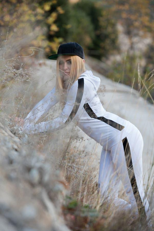 Νέα γυναίκα στο σχεδιάγραμμα που φορά sportswear και το καπέλο γυναικών στοκ εικόνα με δικαίωμα ελεύθερης χρήσης