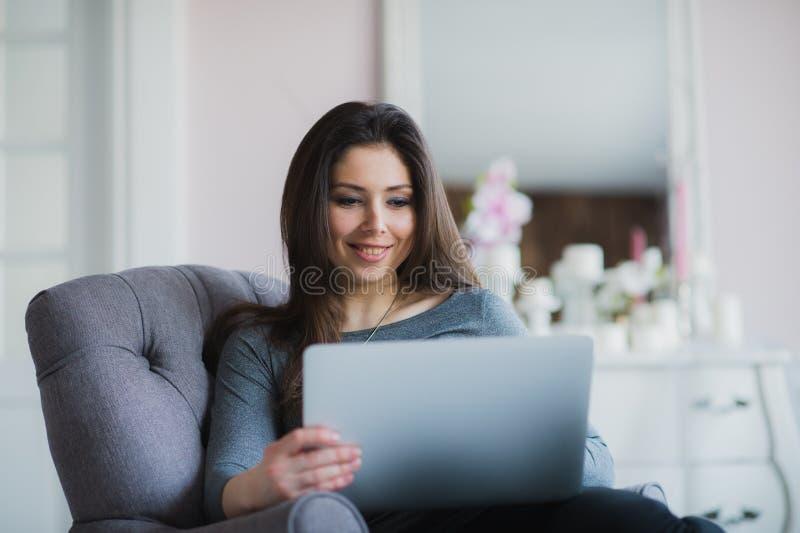 Νέα γυναίκα στο σύγχρονο διαμέρισμα πολυτέλειας, κάθισμα άνετο στον υπολογιστή εκμετάλλευσης πολυθρόνων στις περιτυλίξεις της, χα στοκ εικόνα