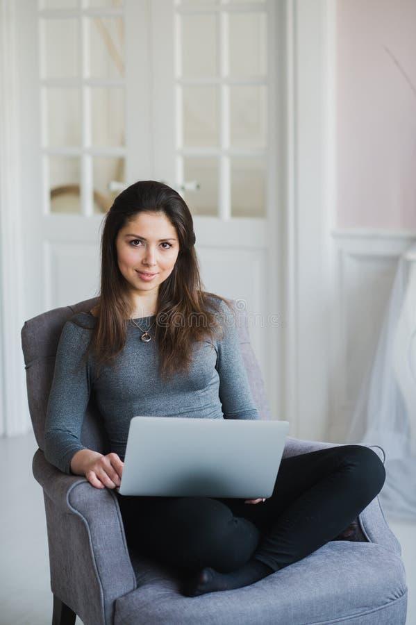 Νέα γυναίκα στο σύγχρονο διαμέρισμα πολυτέλειας, κάθισμα άνετο στον υπολογιστή εκμετάλλευσης πολυθρόνων στις περιτυλίξεις της, χα στοκ εικόνα με δικαίωμα ελεύθερης χρήσης