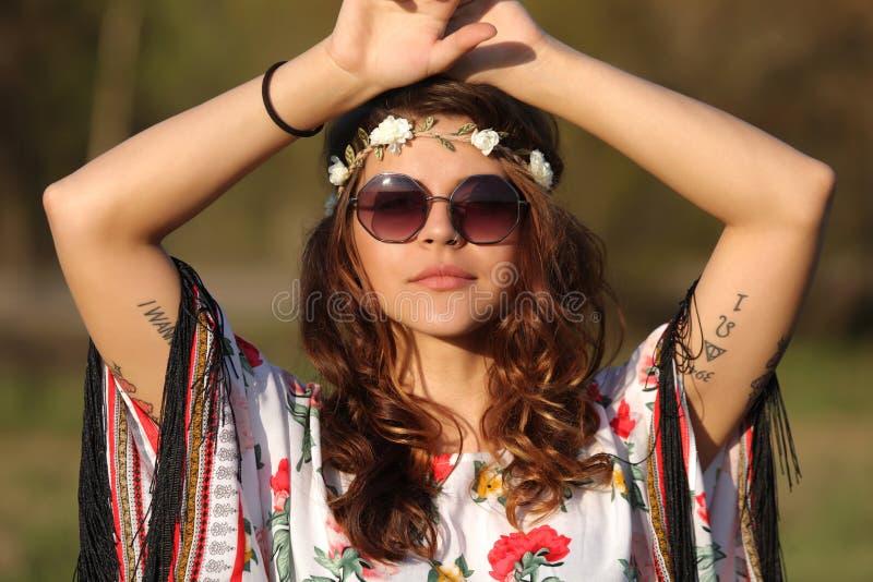 Νέα γυναίκα στο ύφος χίπηδων που εξετάζει τη κάμερα και που κρατά τα χέρια στο κεφάλι υπαίθρια στοκ εικόνες