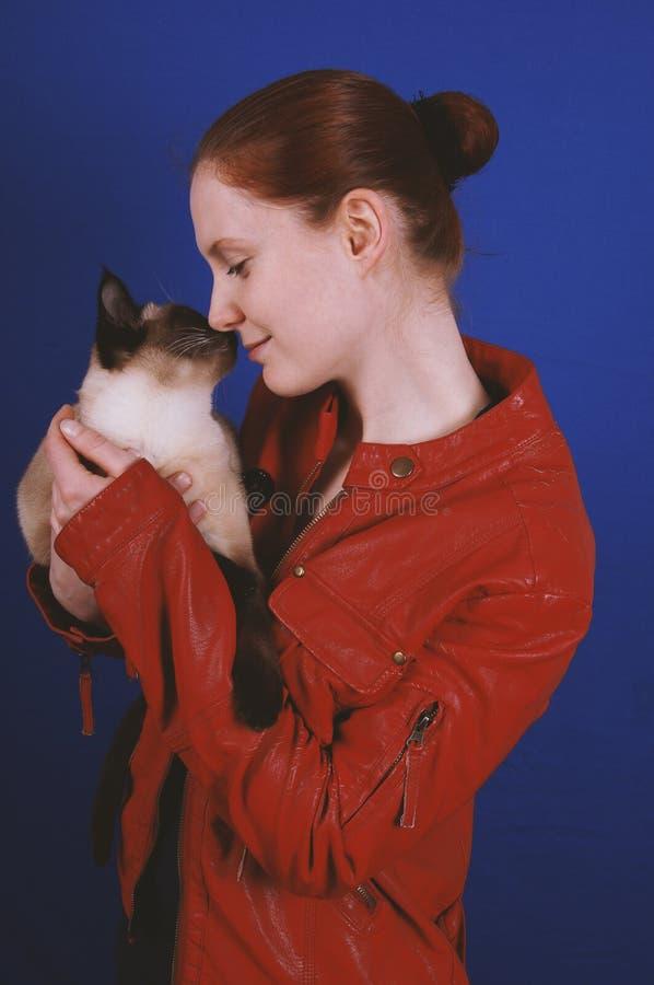 Νέα γυναίκα σχετικά με τις μύτες με τη γάτα στοκ εικόνες