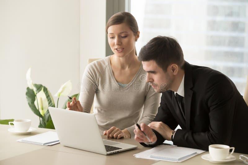 Νέα γυναίκα υπάλληλος που παρουσιάζει υπολογισμούς στον προϊστάμενο στοκ φωτογραφία με δικαίωμα ελεύθερης χρήσης