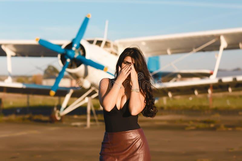 Νέα γυναίκα φοβισμένη να πετάξει ένα αεροπλάνο για το ταξίδι Η στάση κοντά στο αρχαίο αεροπλάνο κλείνει το πρόσωπό της με τα χέρι στοκ εικόνες με δικαίωμα ελεύθερης χρήσης