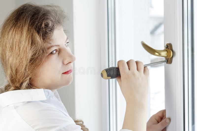 Νέα γυναίκα 30 χρονών ξεβιδώστε τη βίδα με ένα κατσαβίδι I& x27 μ που πηγαίνει να καθορίσει τη μάνδρα στο γυαλί στοκ φωτογραφία με δικαίωμα ελεύθερης χρήσης