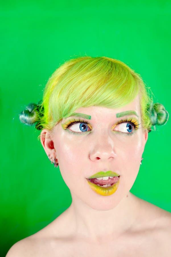 Νέα γυναίκα Beautyful με την πράσινη τρίχα που γλείφει το χείλι της στο πράσινο υπόβαθρο στοκ φωτογραφίες
