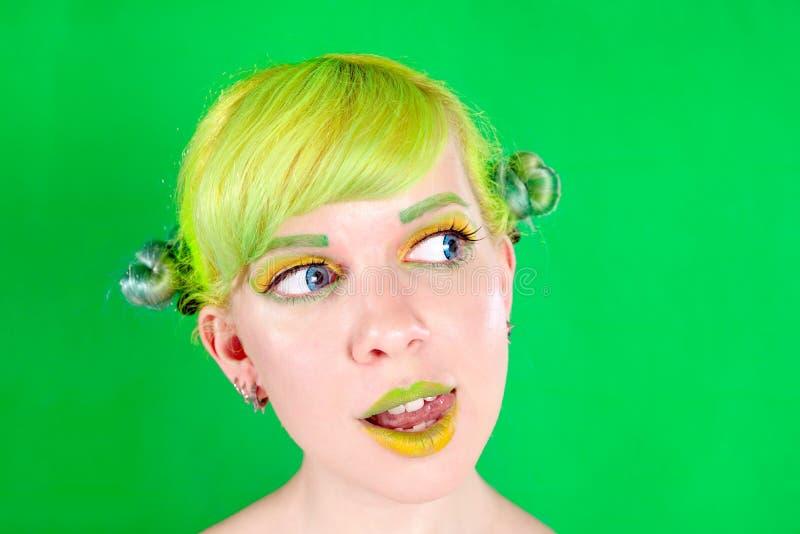 Νέα γυναίκα Beautyful με την πράσινη τρίχα που γλείφει το χείλι της στο πράσινο υπόβαθρο στοκ φωτογραφία με δικαίωμα ελεύθερης χρήσης
