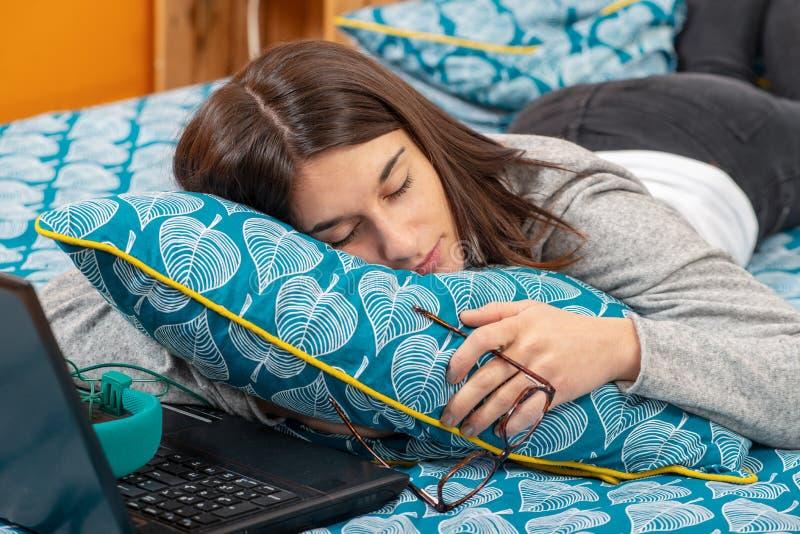 Νέα γυναίκα brunette κοιμισμένη με το lap-top στο κρεβάτι στοκ φωτογραφία