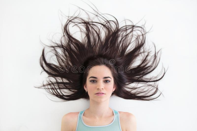 Νέα γυναίκα brunette με το όμορφο hairstyle που βρίσκεται στο πάτωμα στοκ εικόνες
