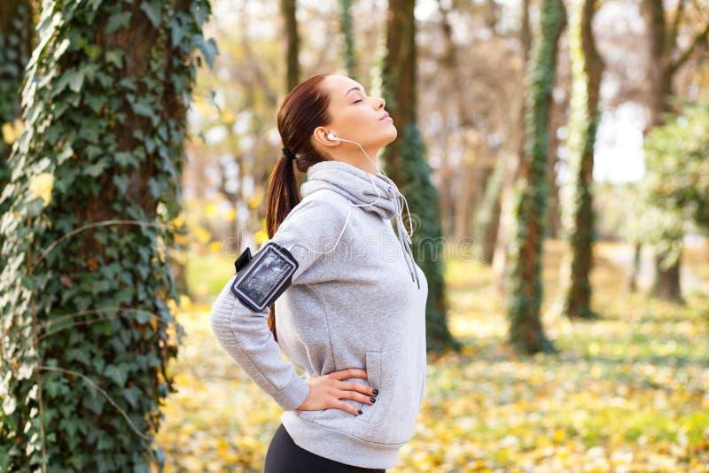 Νέα γυναίκα brunette που πιάνει την αναπνοή της μετά από να τρέξει στο πάρκο στοκ εικόνες με δικαίωμα ελεύθερης χρήσης