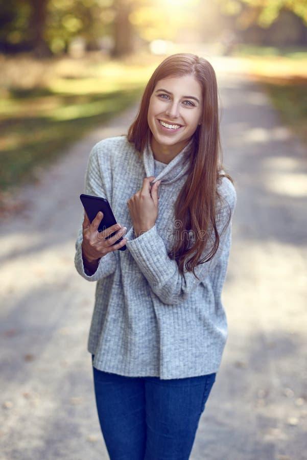 Νέα γυναίκα brunette στο γκρίζο πουλόβερ και τζιν παντελόνι που χρησιμοποιούν το μεγάλο smartphone στοκ εικόνες με δικαίωμα ελεύθερης χρήσης